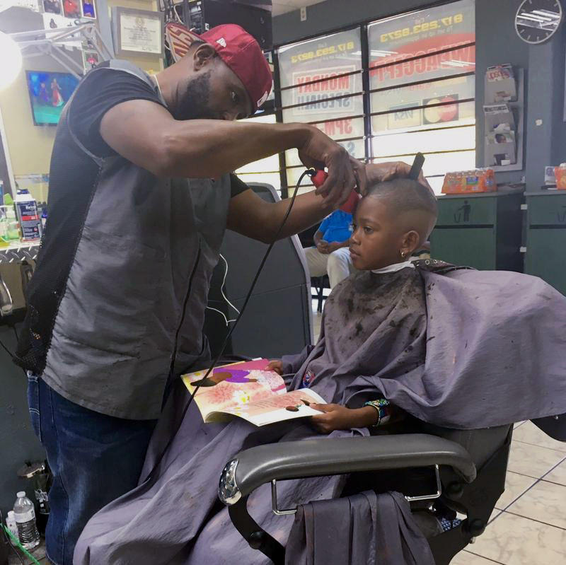 Cooper Evan Ross, who turns 6 years old this month, is learning how to read sight words. He says he likes picking out a different book every time he visits his barber, Tyrone Malone, at Millennium Cuts in Fort Worth.