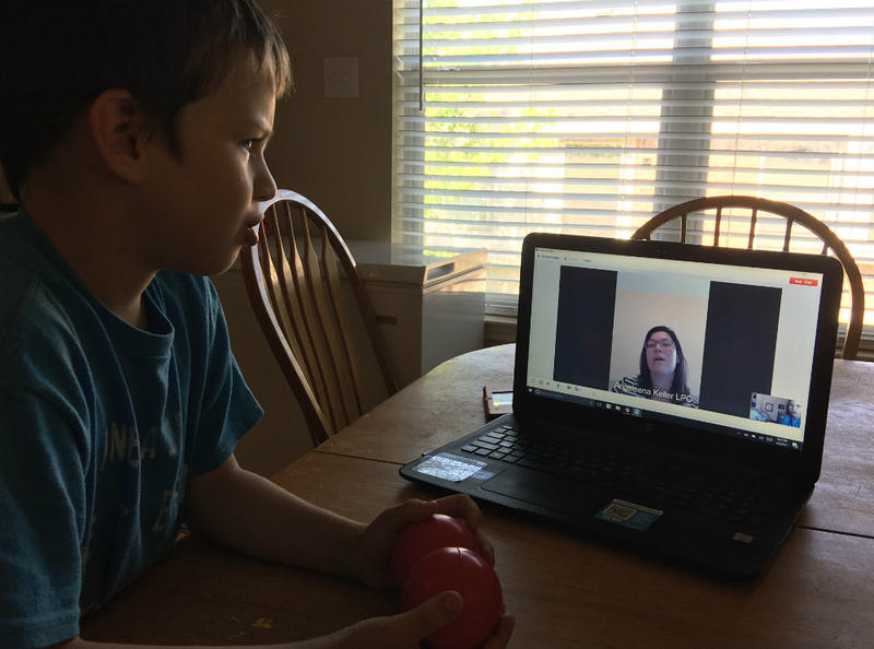 Josh Masters listens to Children's Health licensed counselor Angeleena May using the hospital's telehealth connection. Children's Health now has more than 100 telehealth school partners.
