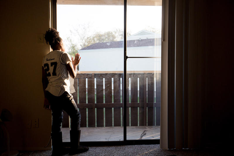 Jamyri White looks out an apartment window in Fort Worth. White and her family are evacuees from Hurricane Harvey.