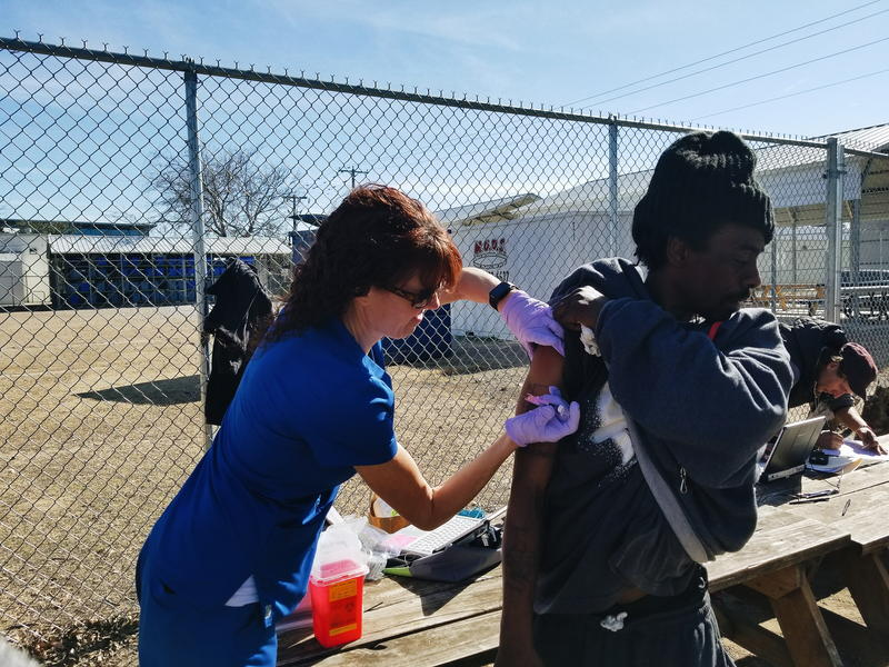 Alicia Coomes gives Michael Houston a flu shot at the roving flu clinic station, set up to help Fort Worth's homeless.