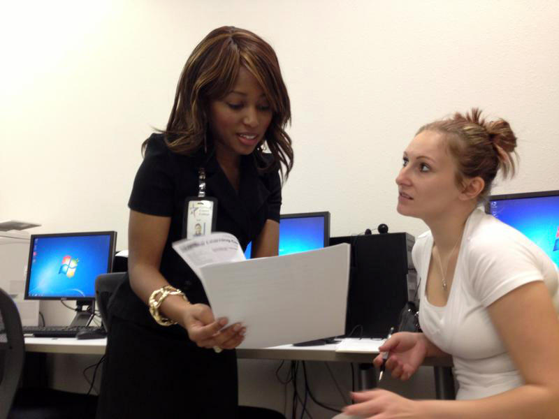 Sharee Davis talks to Crystal Jordan, one of the students in her GED test prep class at the Eastside Workforce Center in Fort Worth in January 2014. Jordan dropped out of school in the 8th grade.