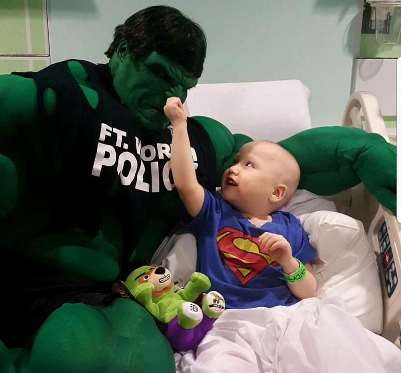 Fort Worth Police Officer Damon Cole visits a patient at Cook Children's Medical Center dressed as the Incredible Hulk.