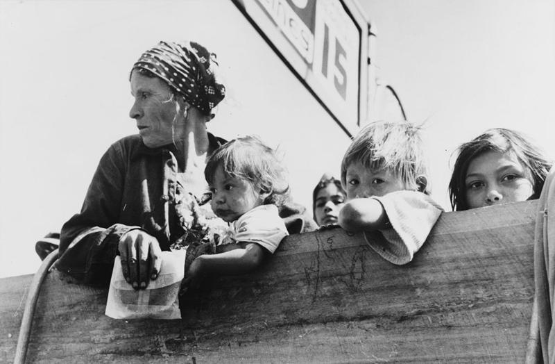 Mexican woman and children looking over side of truck at a filling station in Neches, Texas. They are being deported due to white trade unions wanting their jobs back. October 1939.