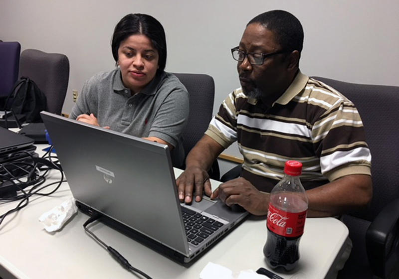 Jisenia Smith (left) and Percy Windom (right) in NPower's tech fundamentals class work on configuring wireless routers.