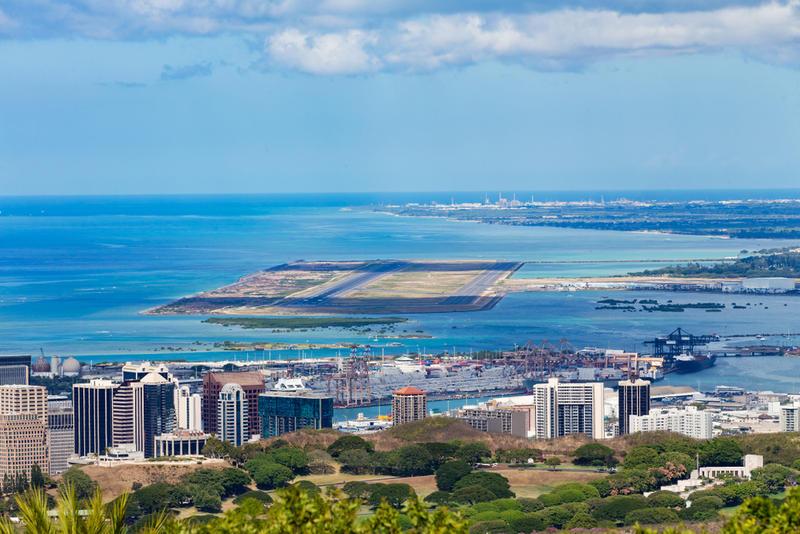 Elevated view of the Daniel K. Inouye International Airport, Oahu, Hawaii with the Pacific Ocean behind.