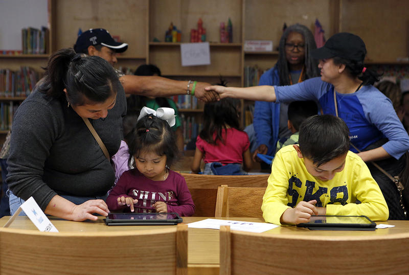 Thelma Gomez (left) and her children, Hady Martinez, 2, and Nicolas Rojas, 4, work on tablets in the library during Parent Night at Mitchell Boulevard Elementary School in Fort Worth on March 8, 2018.