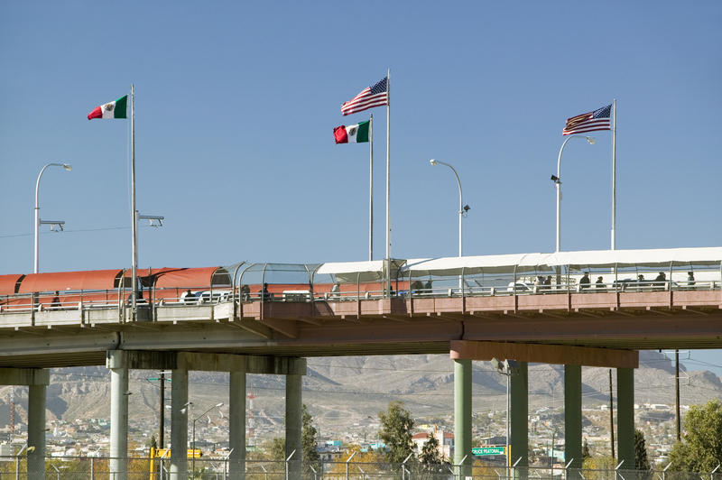 The border of Mexico and the United States, with flags and a walking bridge connecting El Paso to Juarez, Mexico.