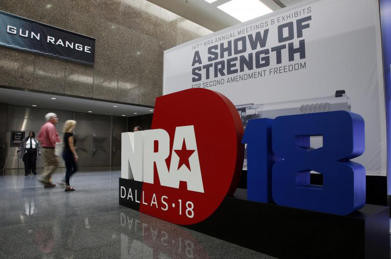 People walk by NRA convention signage in the Kay Bailey Hutchison Convention Center in Dallas on Thursday.