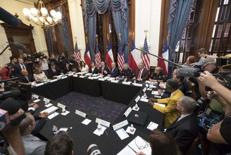 Gov. Greg Abbott (top center, in front of U.S. flag) held the first of three roundtable discussions on school safety in the aftermath of the Santa Fe high School shooting, in Austin on May 22, 2018.