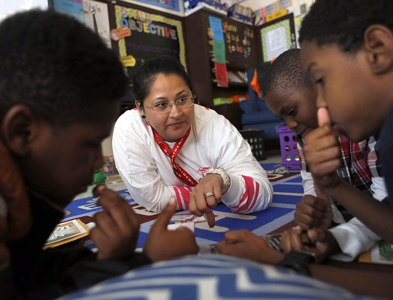Teacher Marjorie Garay works with fourth-graders (from left) Lance Moss, Andre Gill, and Katanga Minimums on adding and removing sentences during a writing camp at Mitchell Boulevard on April 3, 2018.