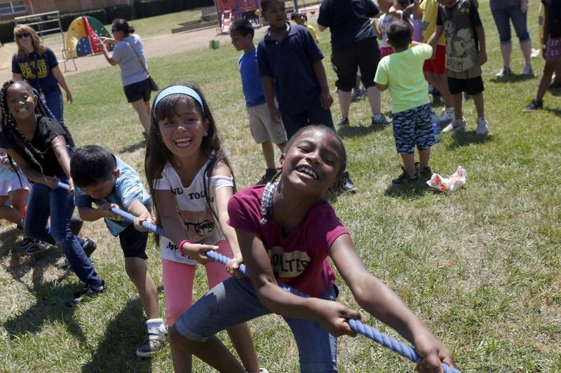 Second-graders Taqiyyvia Paster (right) and Kaelly Morgado (left) play tug-of-war during Field Day at Wimbish Elementary in Arlington on May 18, 2018.