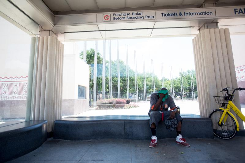 Chris Crowley, 39, takes a break from walking to the DART station from his home in Dallas, Texas.
