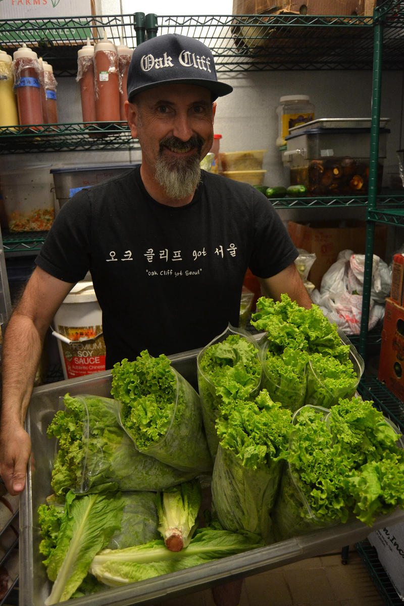 bbbop chef-owner Greg Bussey shows off some of Voeun Tath's lettuce in the restaurant's kitchen.