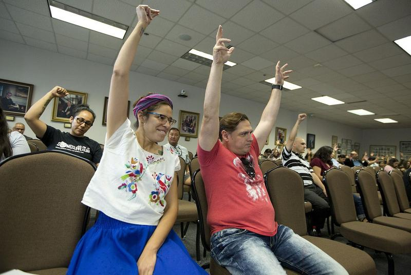 "Devyn Gonzales and Gilberto Sanchez raise their arms in support of changing the name of a new course on Mexican-American history to ""Mexican-American Studies"" at a State Board of Education hearing on Tuesday."