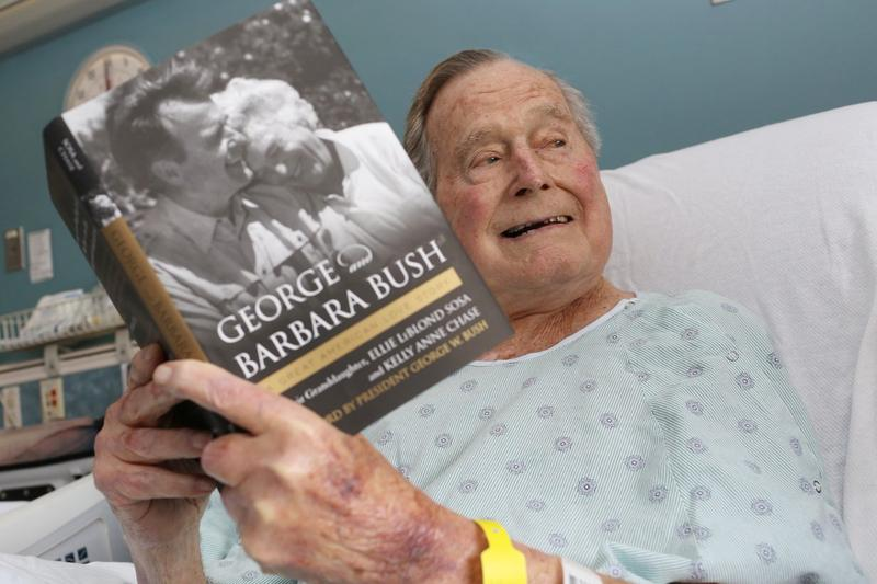 """Former President George H.W. Bush tweeted this photo on June 1, saying: """"Enjoying a great book and a wonderful walk down memory lane this morning. Yet another reminder of just how lucky I have been in life. Very proud of the author and co-author too."""""""