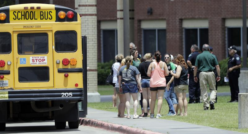 Students wait to enter Santa Fe High School in Santa Fe, Texas, on May 19, 2018, a day after a gunman opened fire in the school, killing several people.