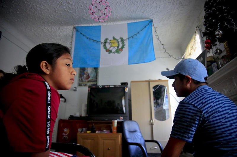 Manuela Adriana, 11, left, sits with her father, Manuel Marcelino Tzah, inside their Brooklyn apartment hours after her release from immigrant detention on July 18. The Guatemalan asylum seekers were separated May 15 at the Texas border.