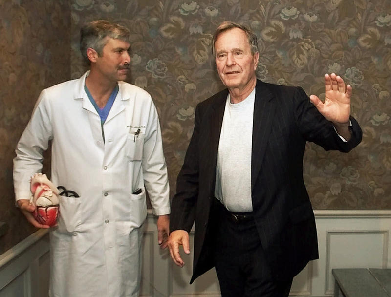 In this Feb. 25, 2000, photo, former President George H.W. Bush waves as he leaves Methodist Hospital with cardiologist, Mark Hausknecht. Hausknecht, who once treated the former president, was fatally shot by a fellow biker on Friday, July 20, 2018.