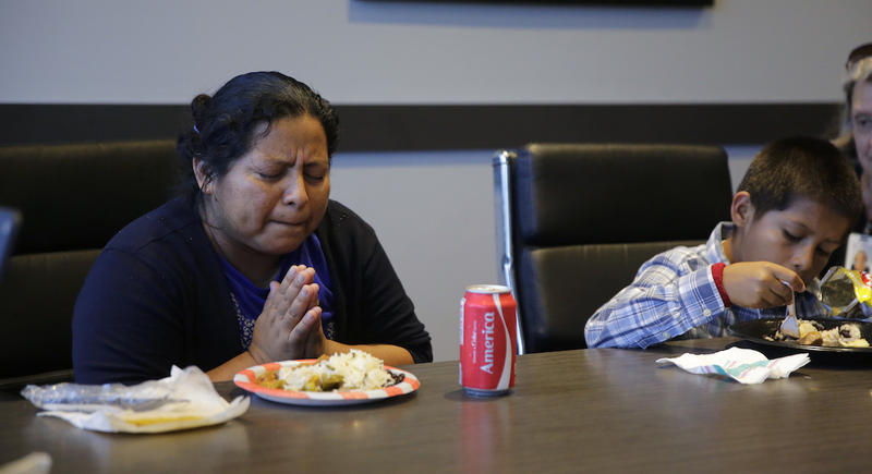 Asylum-seeking immigrant Sandra Soto Cruz prays over her food after she arrived at a Catholic Charities facility with her son after they were reunited on July 23, 2018, in San Antonio.