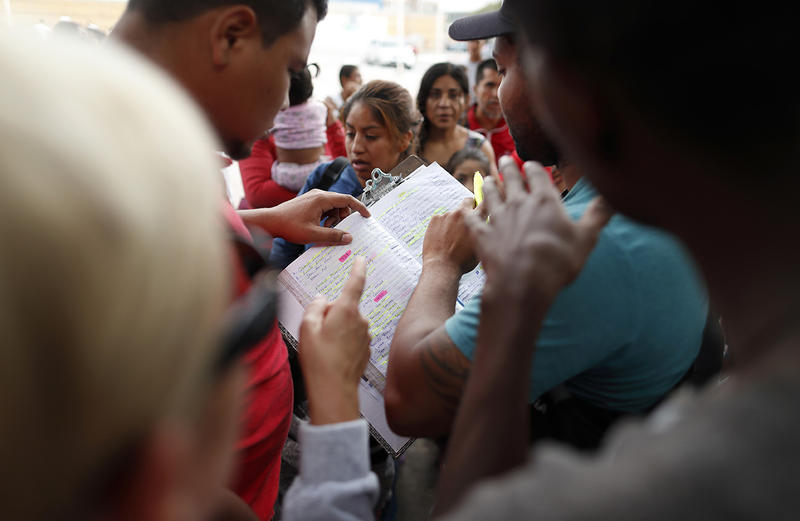 Names are read off a list of people who will cross into the United States to begin the process of applying for asylum Thursday, July 26, 2018, near the San Ysidro port of entry in Tijuana, Mexico.