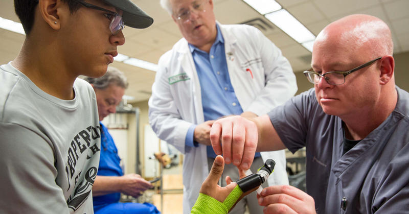 Dr. Todd Dombroski, center, oversees the inital testing of a 3D-printed finger.