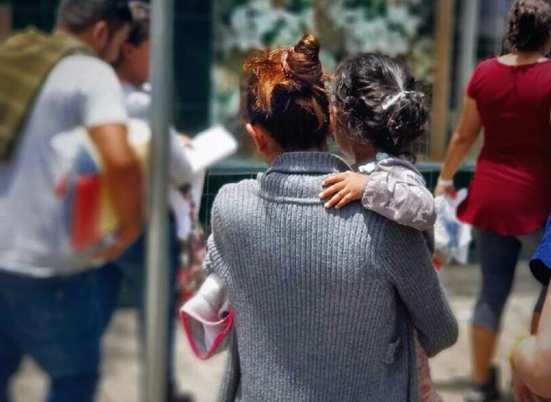 A mother carrying her child in McAllen, Texas, after being released from a U.S Customs and Border Protection Processing Center, in June 2018.