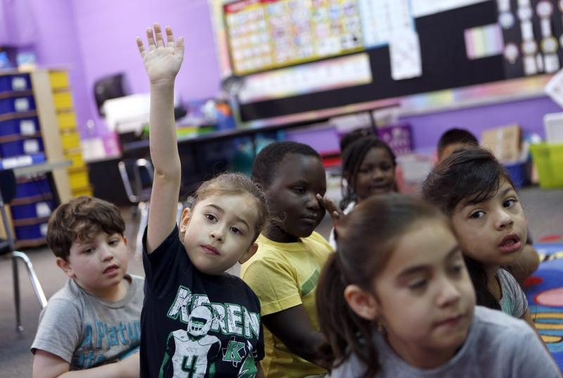 Kindergartner Arabella Morales raises her hand in class at Wimbish Elementary School in Arlington, Texas, on May 21, 2018.