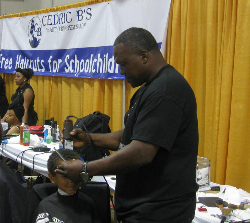Cedric Bolden cuts a child's hair for free at the 2016 Dallas Mayor's Back to School Fair.