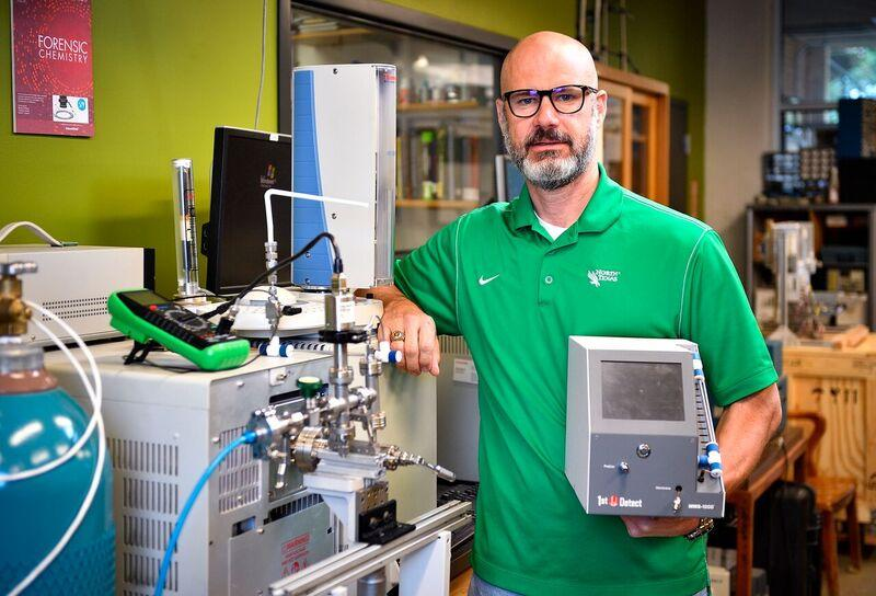UNT chemistry professor Guido Verbeck holds a prototype of the new mini mass spectrometer-based system.