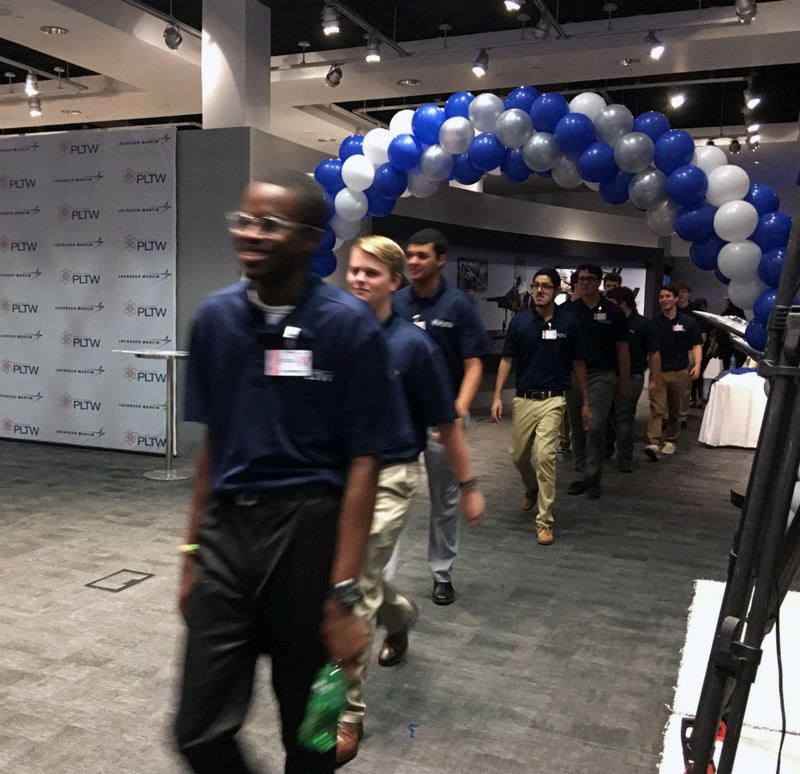 Ozioma Mgbahurike rapidly walks in with fellow high school interns on Lockheed Martin's signing day. Mgbahurike and others will remain interns through college. If everything goes well, they could all get signed to jobs upon college graduation.