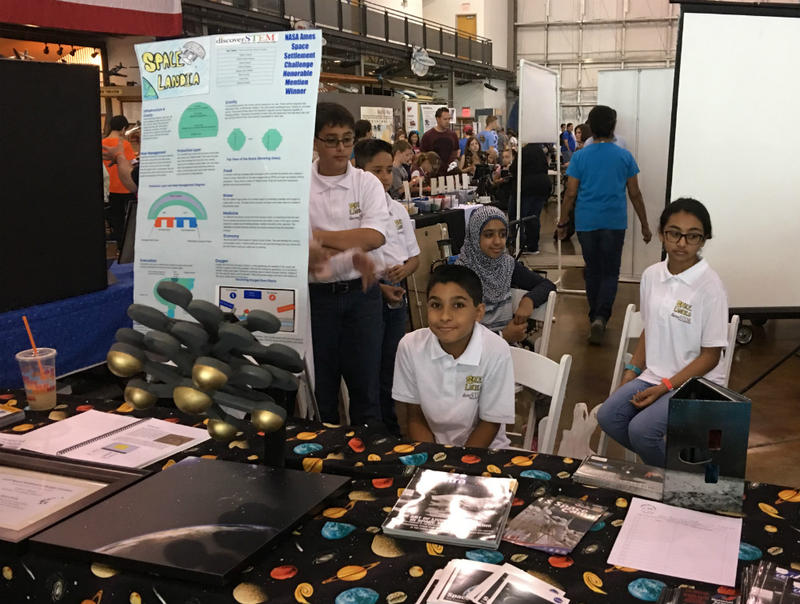 Members of Team Spacelandia at their display table inside of the Frontiers of Flight Museum in Dallas where they show off plans for their space colony.
