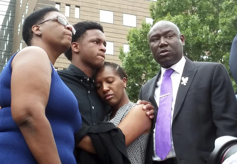 Brandt Jean, center left, brother of shooting victim Botham Jean, hugs his sister Allisa Charles-Findley, during a news conference outside the Frank Crowley Courts Building on Monday in Dallas.