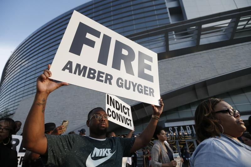 Demonstrators march around AT&T Stadium ahead of an NFL football game between the Dallas Cowboys and the New York Giants in protest of the recent killings of two black men by police, in Arlington, Texas, Sunday.