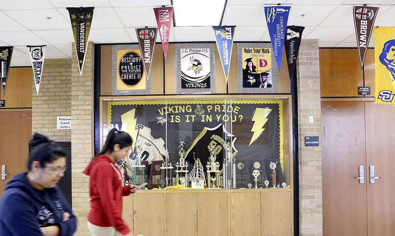 College banners line the hallway at Pinkston High School in Dallas, April 2018.