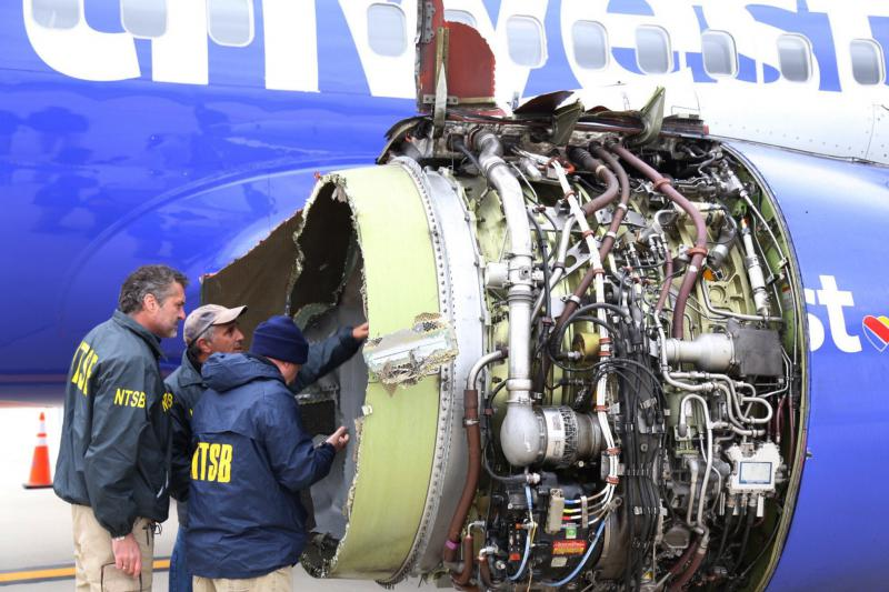 National Transportation Safety Board investigators examine damage to the engine of the Southwest Airlines plane