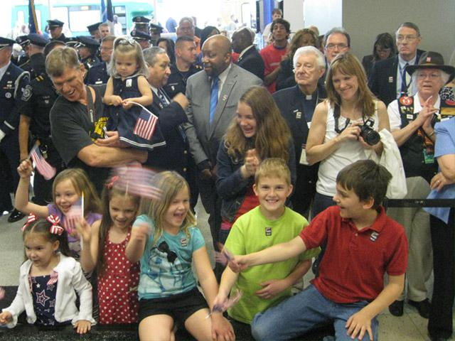 arvey Jones Vietnam vet holding granddaughter with other grandaughters, welcoming troops