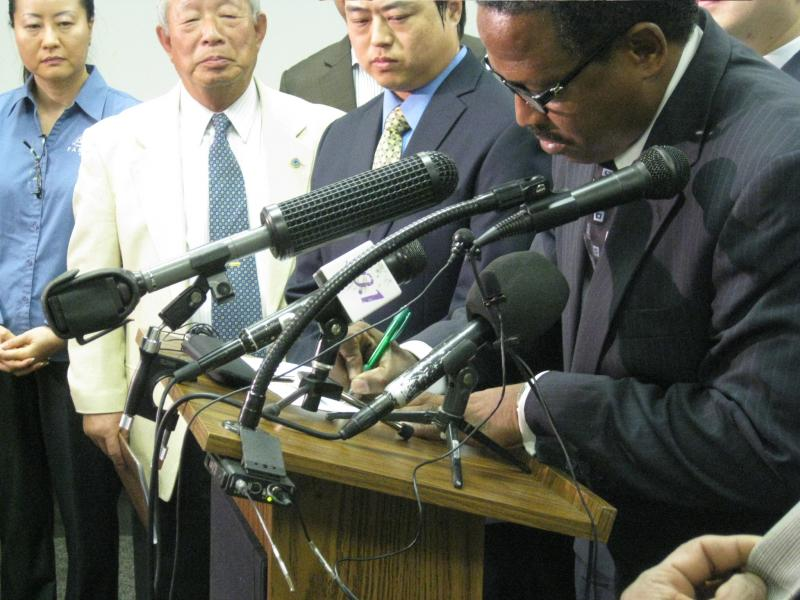 Reverend Ronald Wright signs an agreement as store owner Thomas Pak and other leaders stand with him at a press conference Thursday.