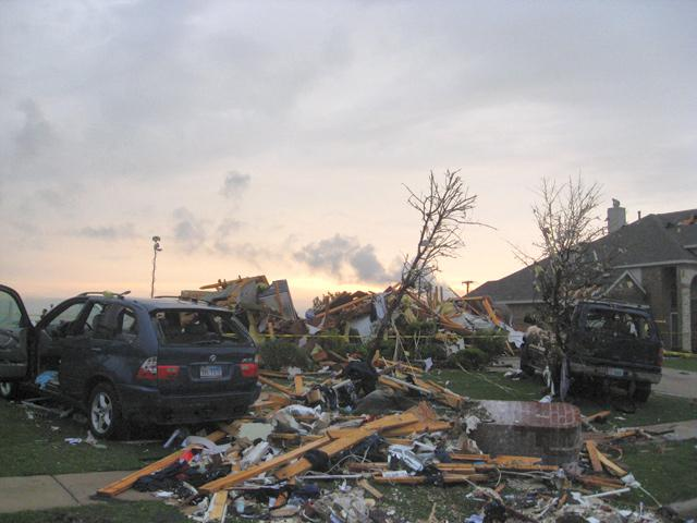 A SUV sits next to a destroyed home in Forney, Texas.