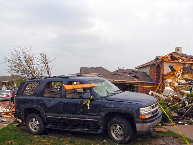 A 2x4 sliced through the windshield of a SUV during the storm.  The car sits next to a destroyed home in Forney.