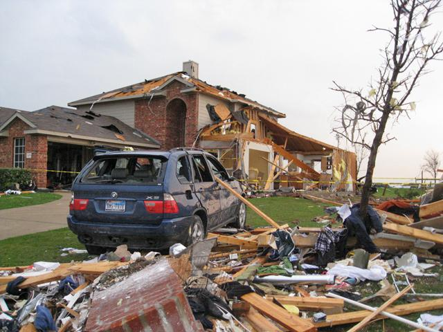 A SUV sits next to a damaged home in Forney.