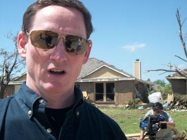 Dallas County Judge Clay Jenkins speaks to press in front of a damaged home on the corner of Roam and Wintergreen Rd.