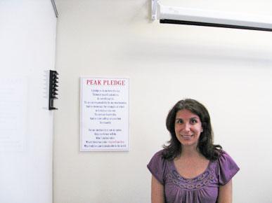 Uplift Education CEO Yasmin Bhatia stands beside the Peak Preparatory campus' credo.