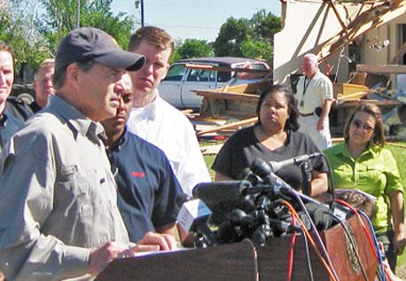 Surrounded by damaged homes and debris, Governor Rick Perry spoke in Lancaster on Thursday. On his right is Lancaster's Mayor Marcus E. Knight