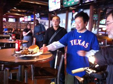 A team from Tokyo Broadcasting inspects a Darvicious burger at BoomerJacks in Arlington.