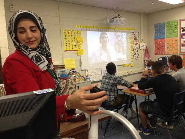 Student teacher Fatina Jalambo holds up a camera so teacher Bilal Douass in Tangier, Morocco can see students he's talking to via Skype. Jalambo, who's teaching at Central Junior High, was born and raised in Kuwait.