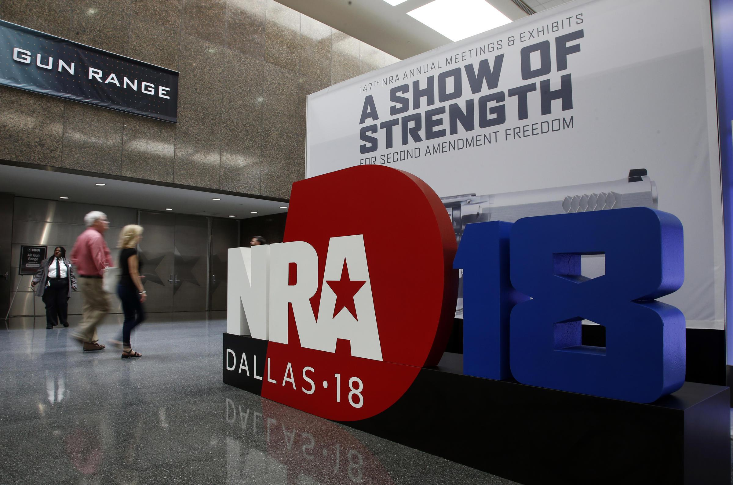 People walk by NRA convention signage in the Kay Bailey Hutchison Convention Center in Dallas on Thursday