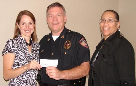 Police Chief Dan Busken accepts a $1,000 donation from Altrusa International members Rose Hayden and Melva Hill