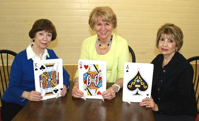 Nancy McFarland, Sharline Freeman and Toni Deaton use giant playing cards as part of the decoration for the upcoming Bridge Event.