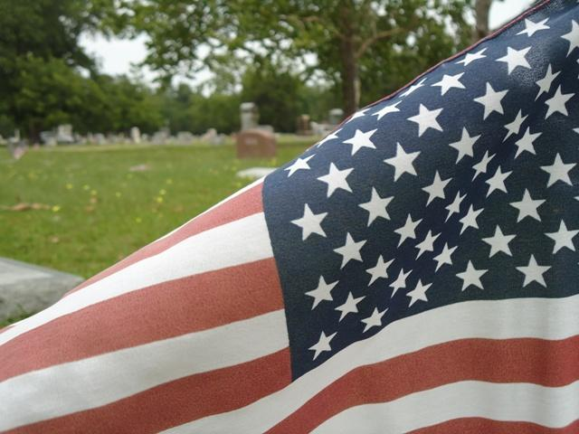 An American flag sits at one of hundreds of graves Saturday at Rosemound Cemetery in Commerce.