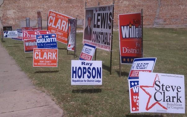 Campaign signs line a section of lawn along Main Street in Commerce.